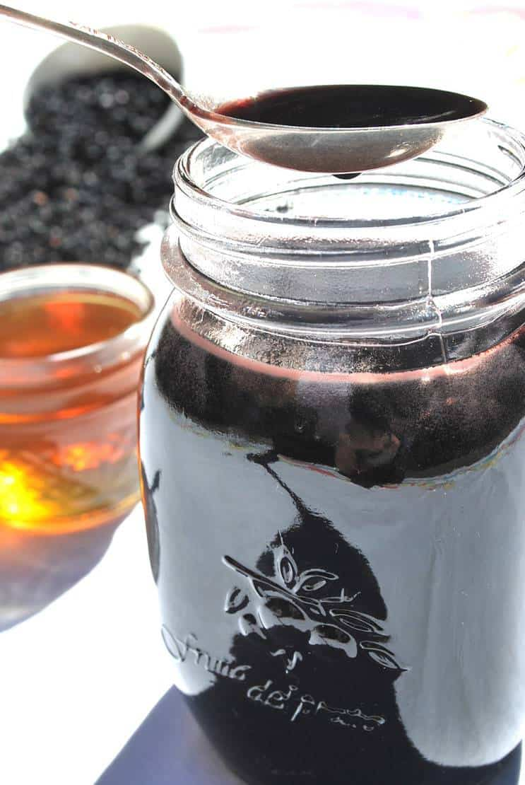 close up of homemade elderberry syrup in jar and on spoon