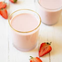 Two glasses of drinkable yogurt on a white wooden surface