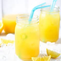 Two mason jars with natural pineapple lemonade and blue straws on a white surface