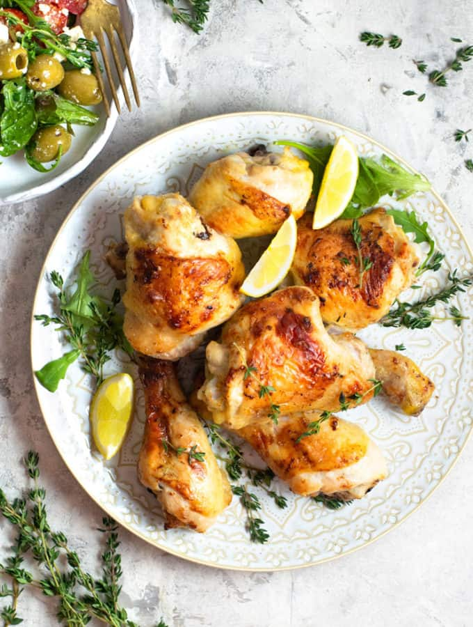 Greek chicken on a plate with lemon wedges and thyme