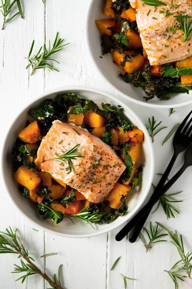 An overhead shot of an easy salmon dinner in two white bowls with squash and kale