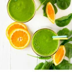 overhead shot of two glasses of orange pineapple green smoothie