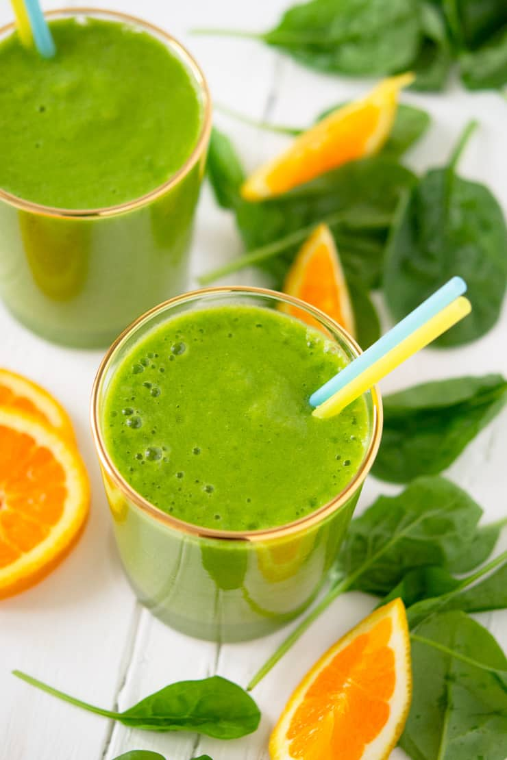 A close up of an orange pineapple green smoothie in a glass with two straws