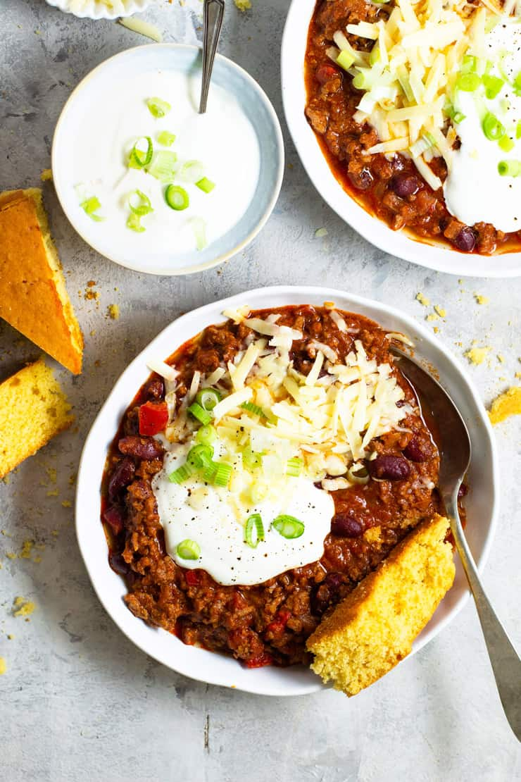 An overhead shot of two bowls of real Texas chili topped with sour cream, cheese and green onions