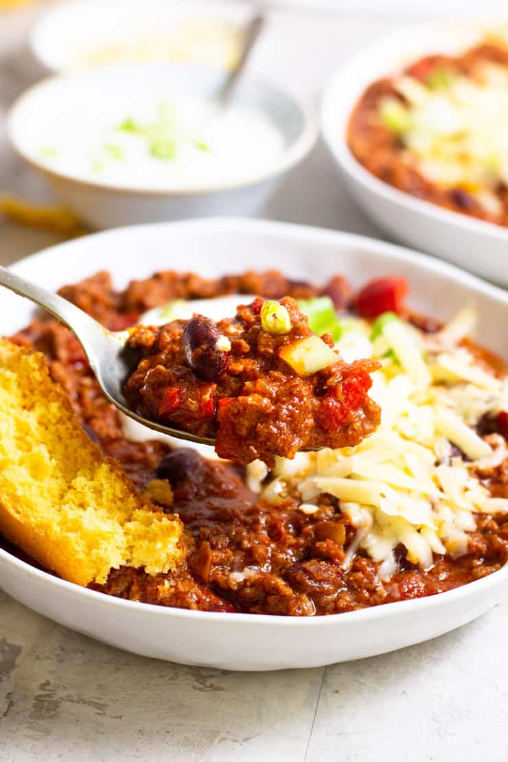 A close up of real texas chili in a bowl with a spoonful on a spoon