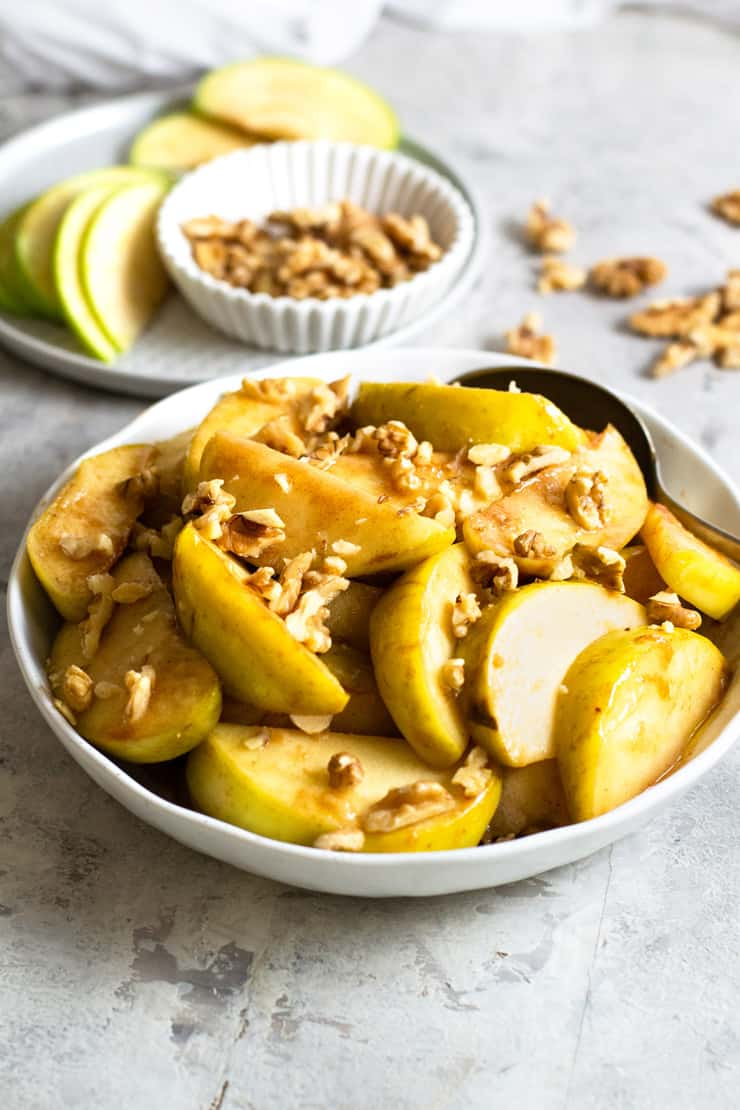 A close up of a bowl of baked apples topped with walnuts