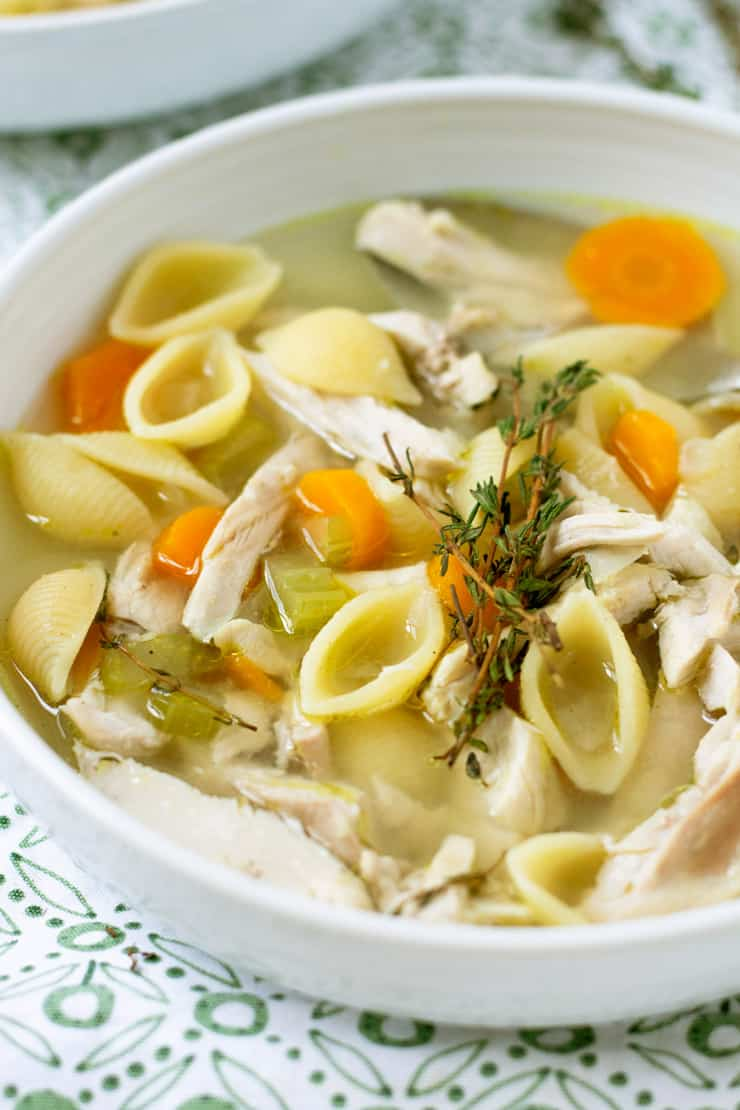 A close up of chicken noodle soup in a white bowl