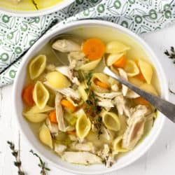 An overhead shot of chicken noodle soup in a white bowl with a spoon