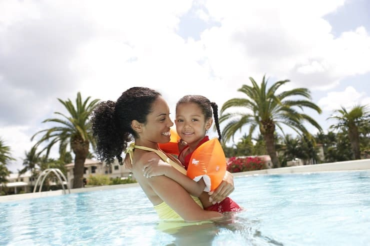 Portrait of smiling mother holding daughter in swimming pool