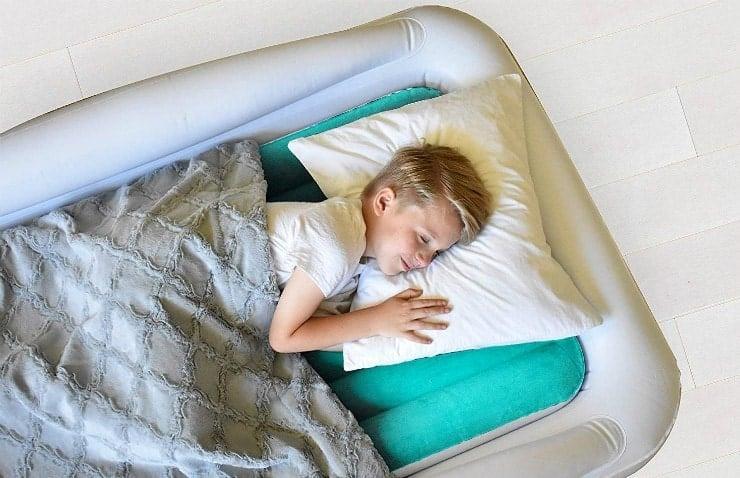 young boy sleeping on inflatable mattress