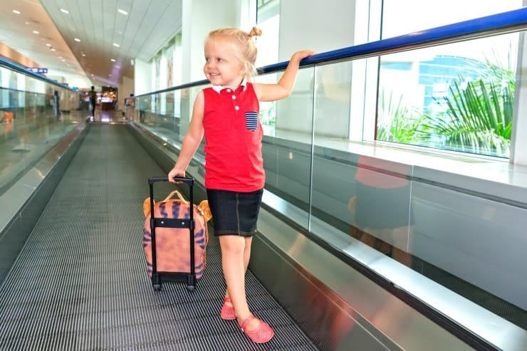 Girl pulling roller backpack carry on through airport