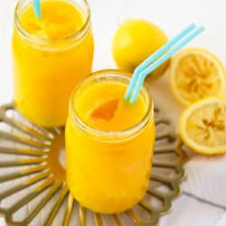 front angle view of two glasses of all natural mango lemonade with teal straws, on gold tray with white background