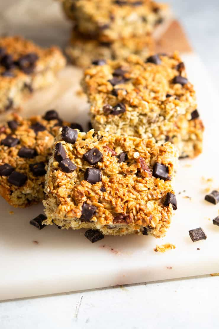 A close up of chocolate chunk oatmeal bars on a marble cutting board