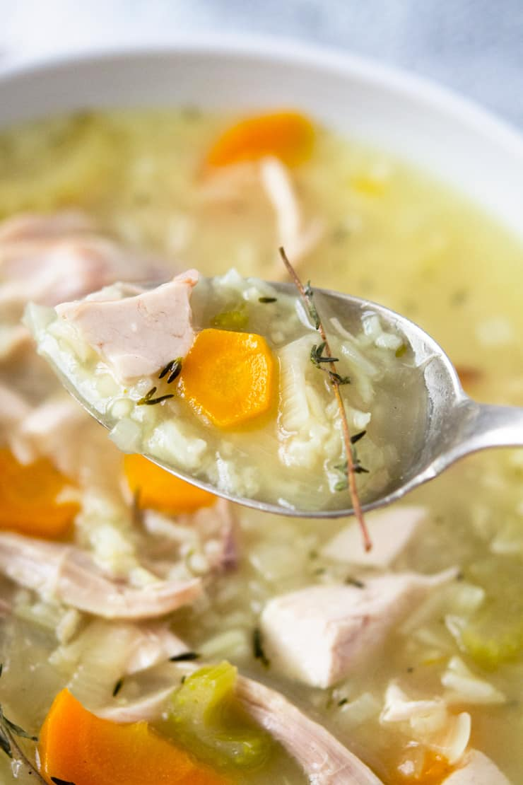 A close up of rotisserie chicken and rice soup on spoon