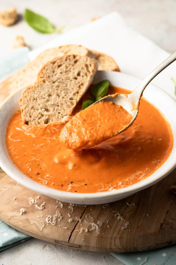 A close up of a spoonful of roasted red pepper soup and slices of bread at the side