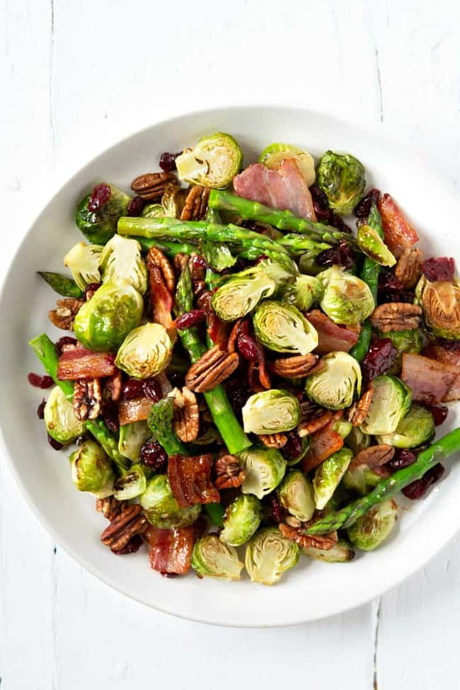 Roasted Brussels sprouts on a plate with asparagus, bacon and pecans