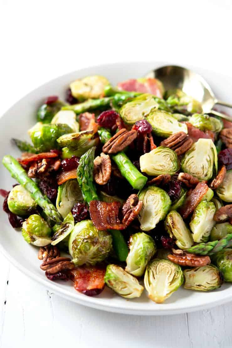 A close up of roasted brussels sprouts with asparagus, bacon and pecans
