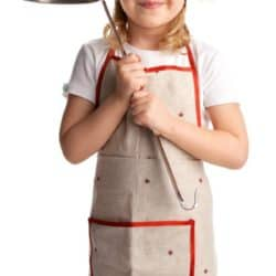 young girl in cooking apron with soup ladle in hand