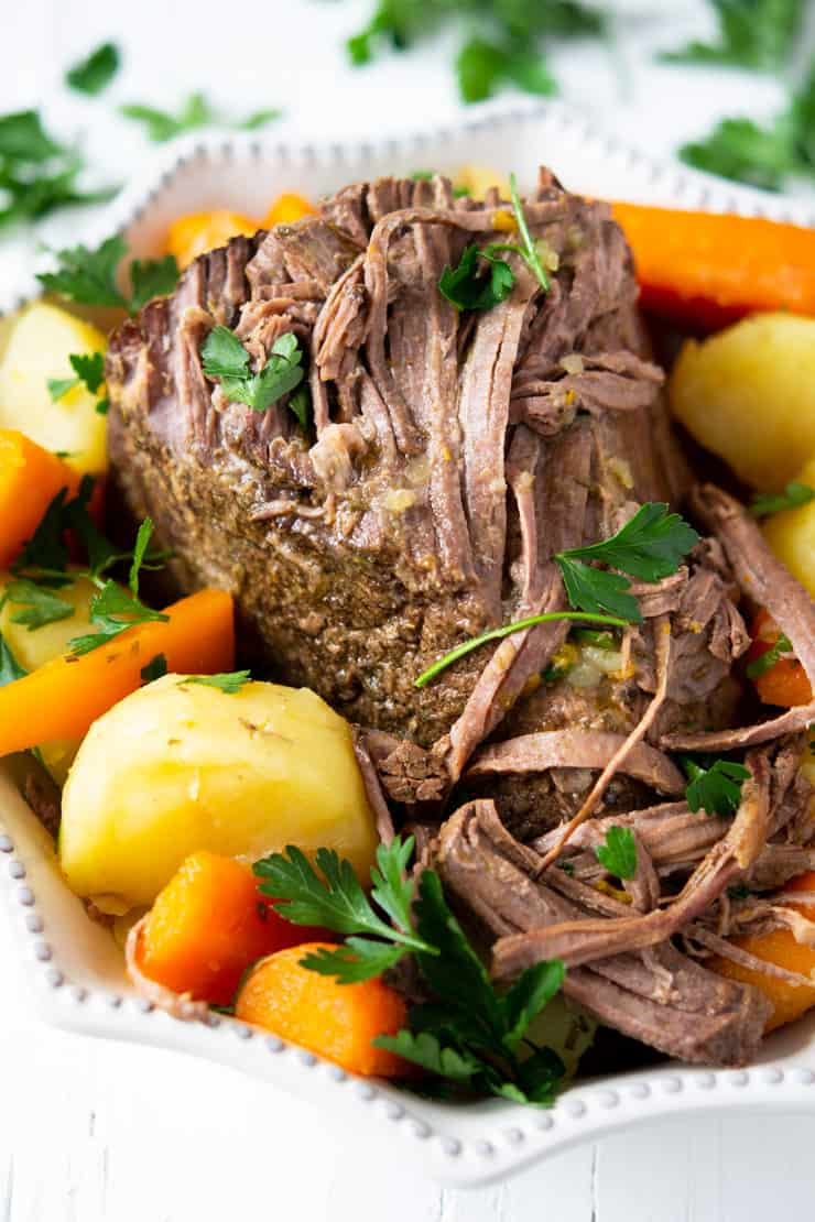 A close up of the best slow cooker beef roast in a serving dish with potatoes and carrots