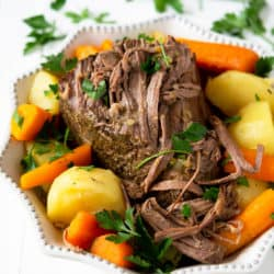 The Best Slow cooker beef roast in a white serving dish with vegetables