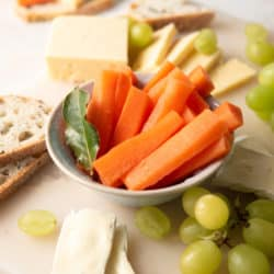 Fermented carrots in bowl with grapes, cheese, and bread scattered around