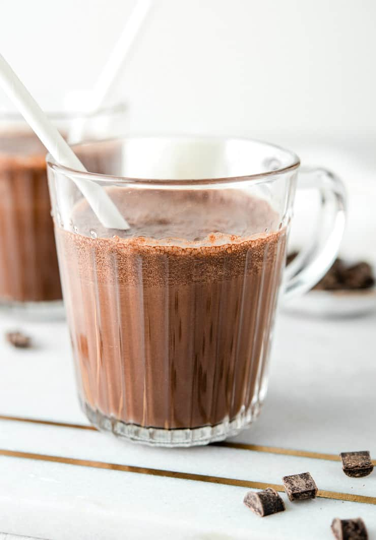 A close up of chocolate milk in a glass with a white straw
