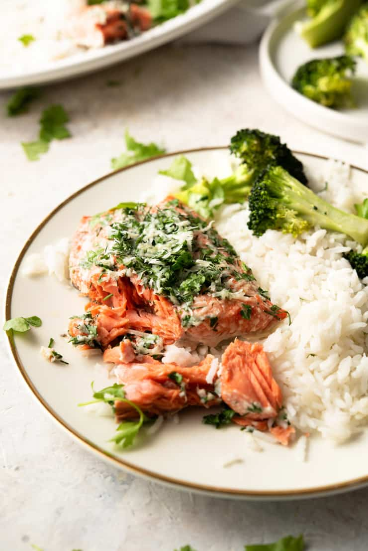 A close up of baked salmon with parmesan crust and herbs on a white plate