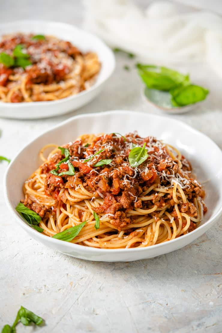 Slow cooker spaghetti sauce in a white bowl topped with basil