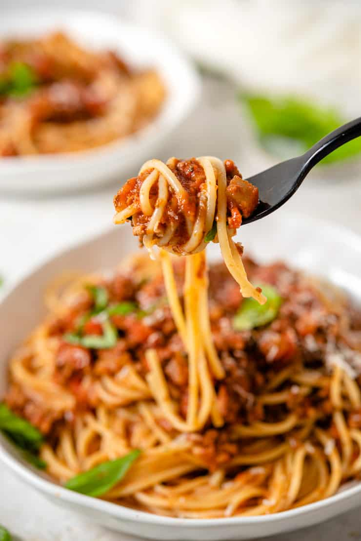 A close up of spaghetti with meat sauce on a fork