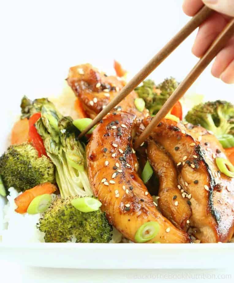 Chopsticks Picking-up Teriyaki Chicken from a White Plate