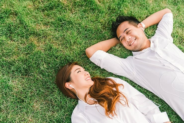 young couple lying in grass together