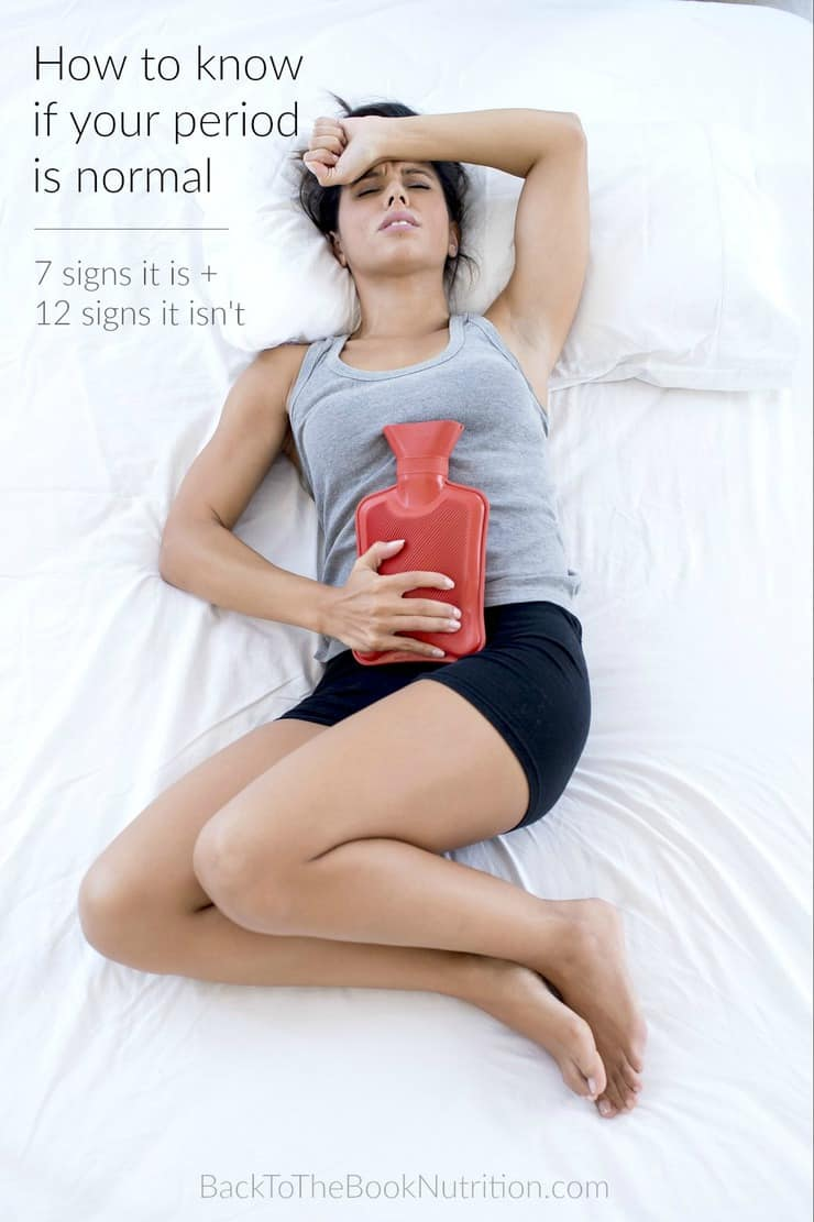 woman lying in bed with hot water bottle on stomach