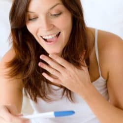 woman excited about positive pregnancy test