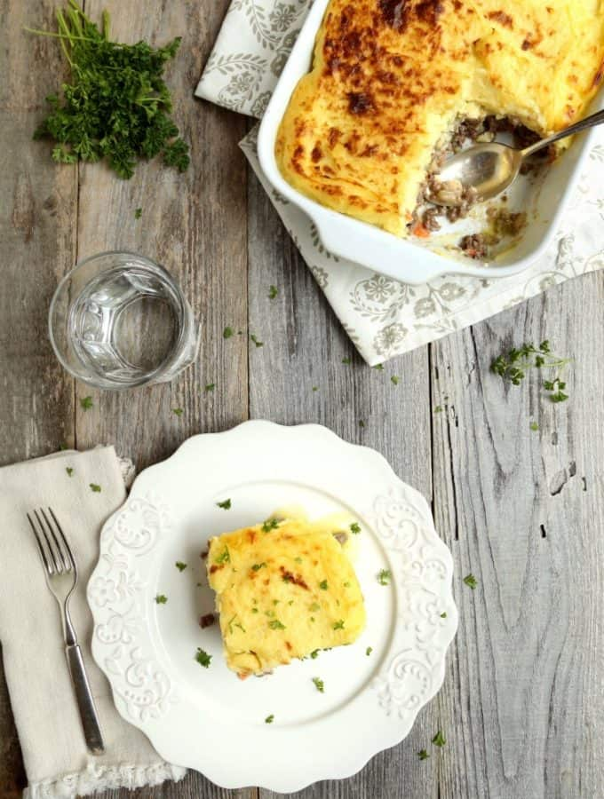 overhead view of cottage pie in pan and one serving on plate