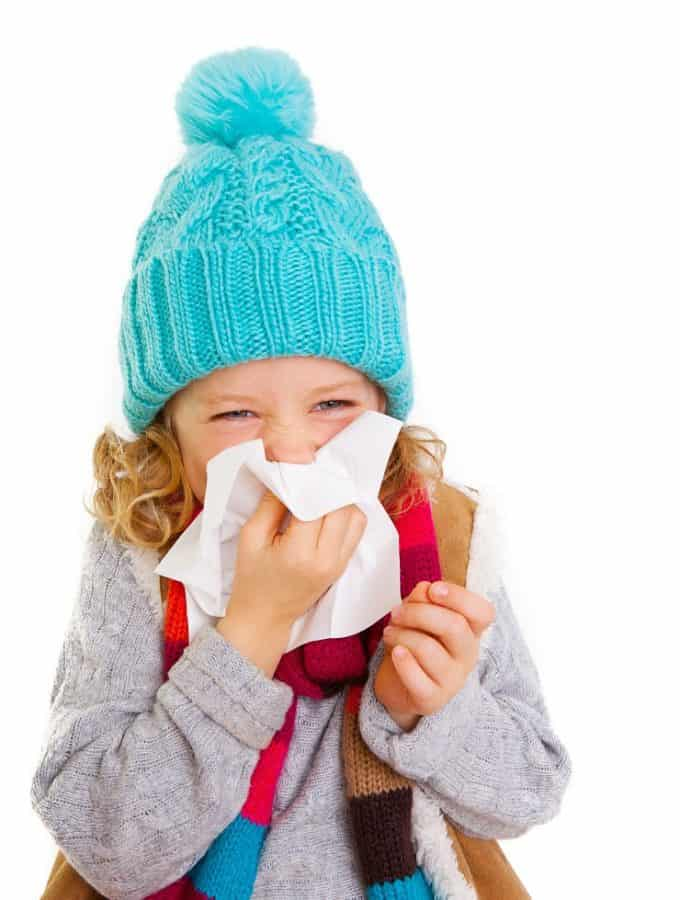 young girl in warm clothing blowing nose