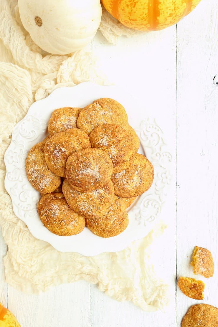 overhead shot of a pile of pumpkin snickerdoodles on plate with white wood background and pumpkins to decorate