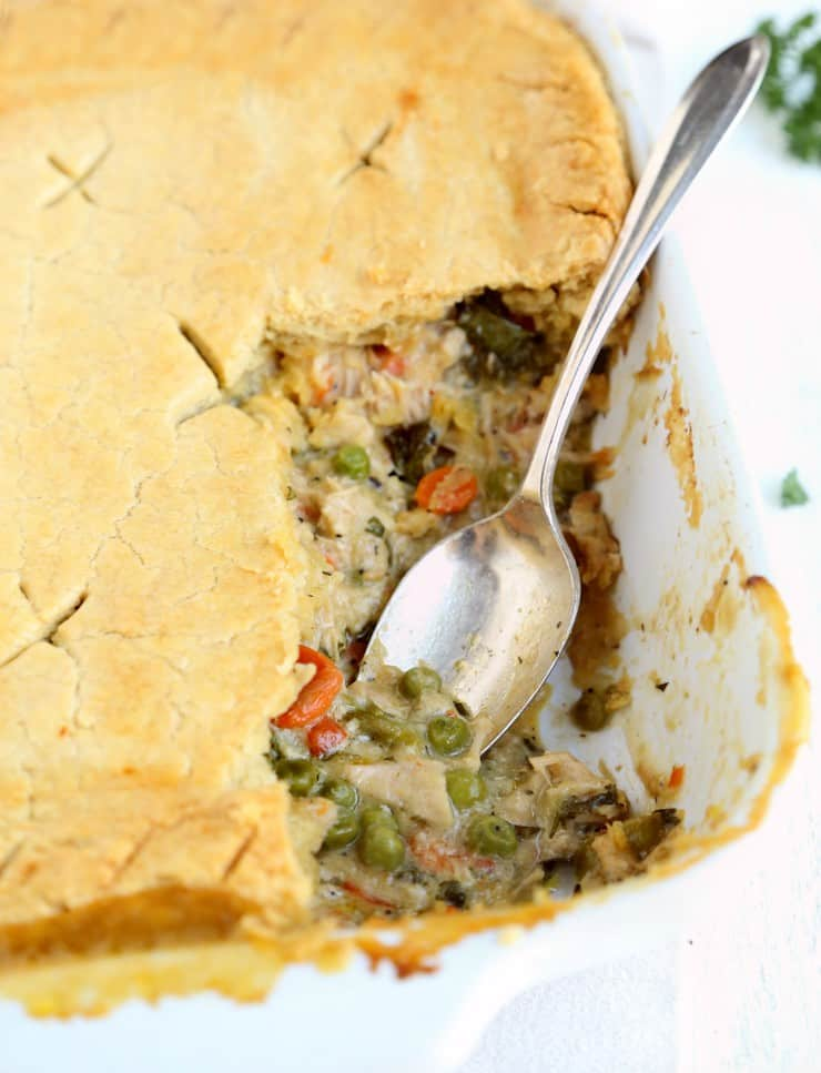 close up of turkey pot pie in pan with 1 serving removed