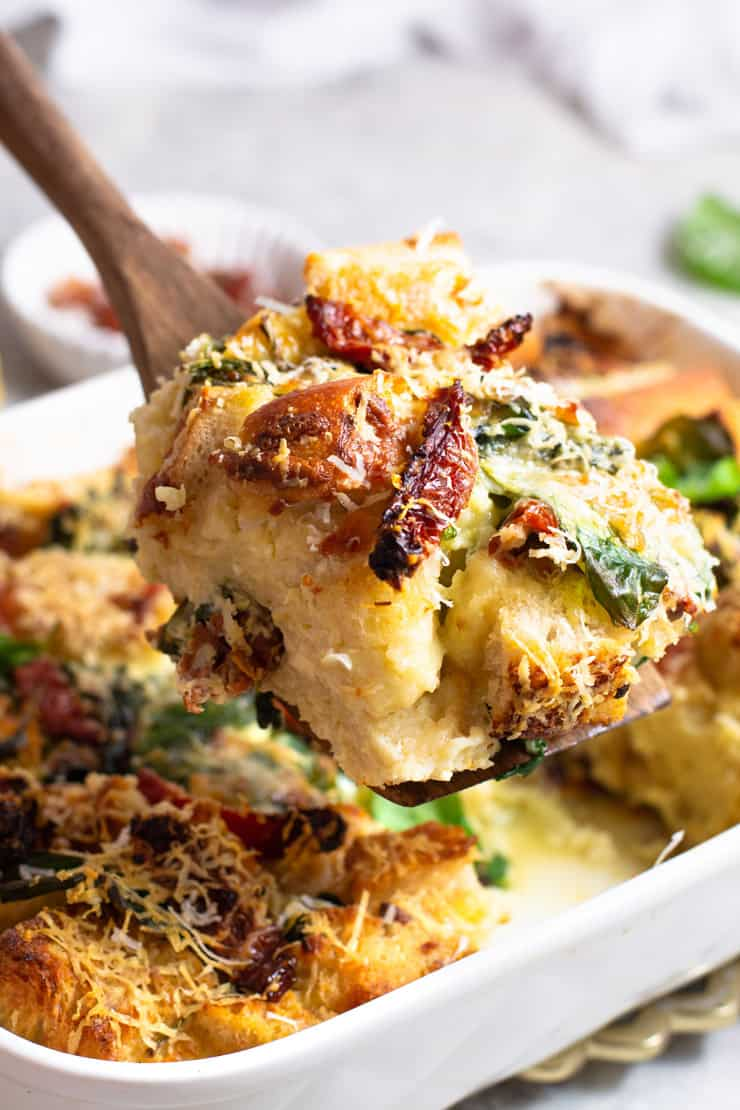 A close up of a slice of breakfast strata with spinach