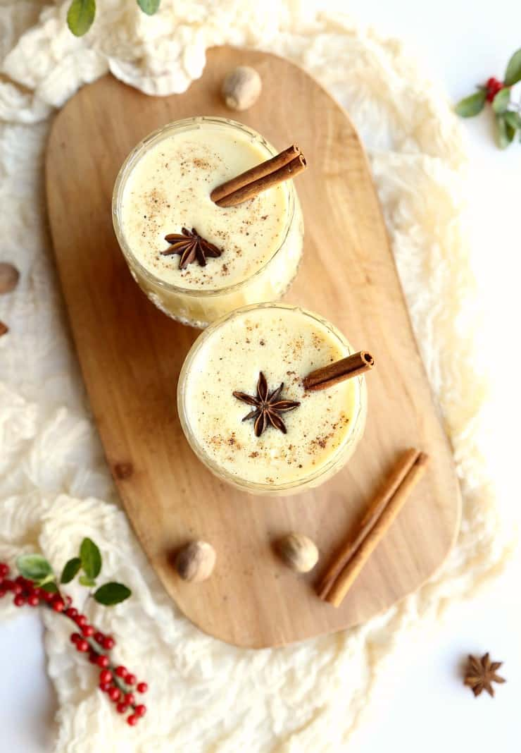 overhead shot of two glasses eggnog on wood tray with cinnamon sticks and spices