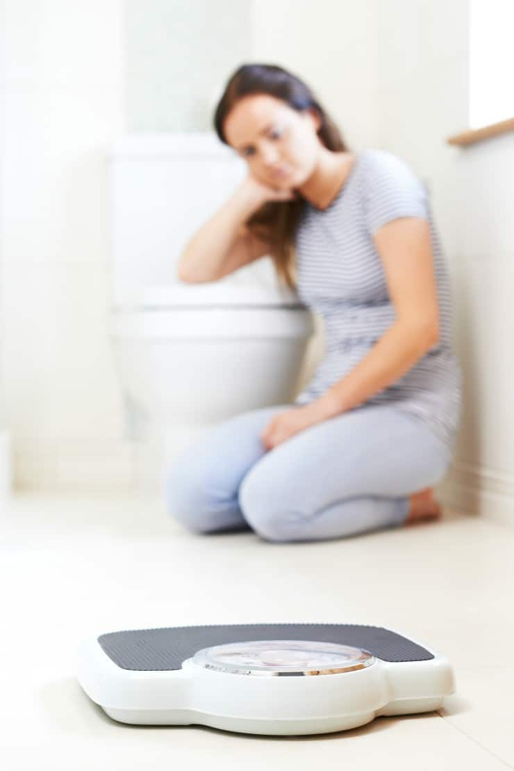 Sad young woman sitting on bathroom floor near scale