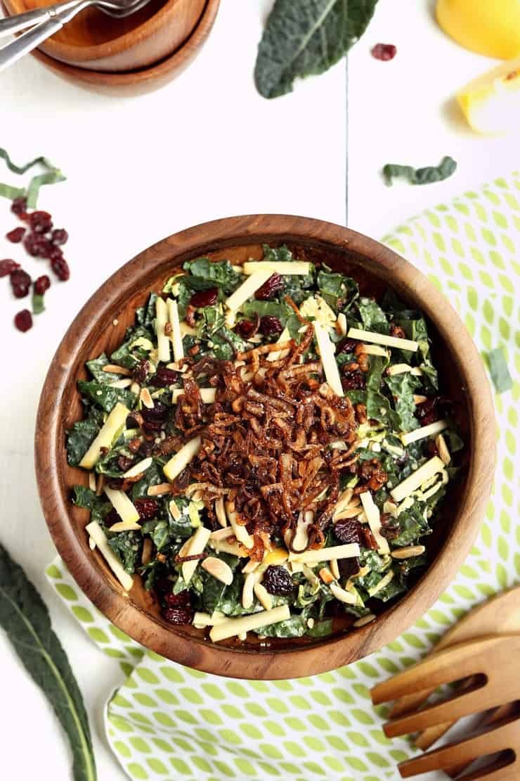 Overhead image of Kale and Brussels Sprouts Super Salad with apples, cherries, almonds, and fried shallots in wooden bowl on white background with extra ingredients sprinkled around