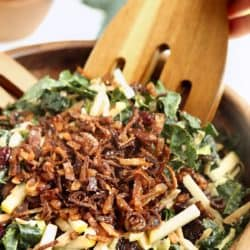 Close up image of Kale and Brusssels Sprouts Super Salad being tossed with wooden tongs in wooden salad bowl