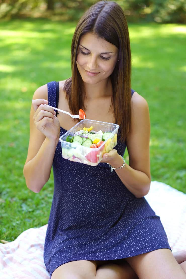 woman eating salad on picnic blanket