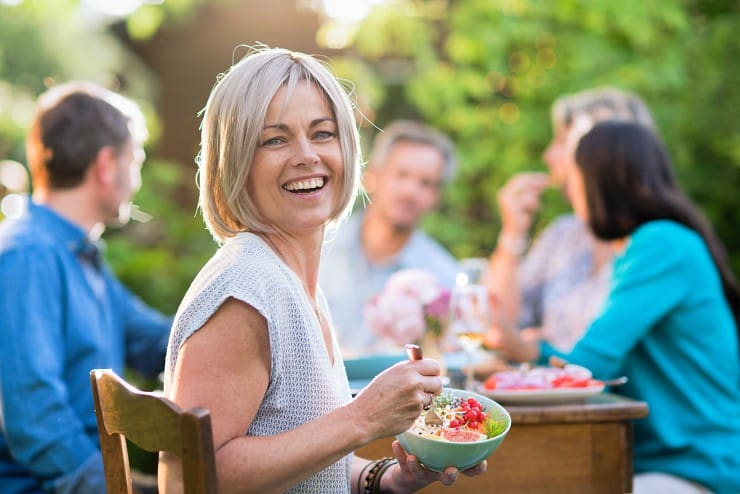 Woman at outdoor dinner party turned toward camera, smiling and holding a bowl of healthy food