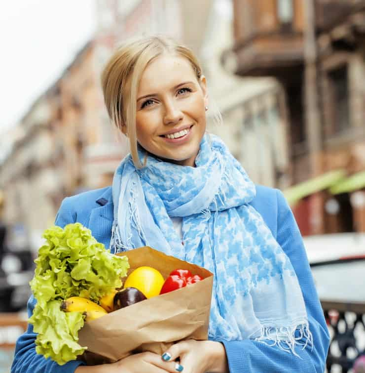 young blond woman with food in bag walking on street healthy cheerful