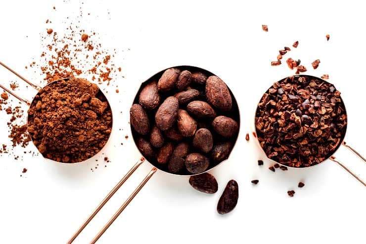 Rose gold measuring cups of cocoa beans, cacao nips and cocoa powder on a white background, flat lay healthy food concept