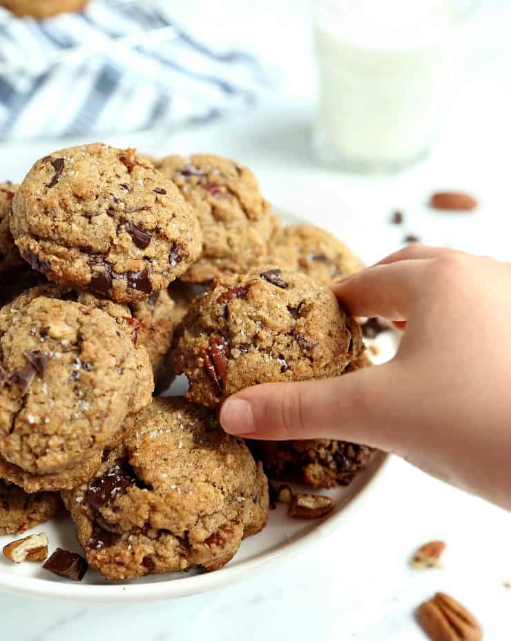 child's hand grabbing a chocolate chunk cookie from pile