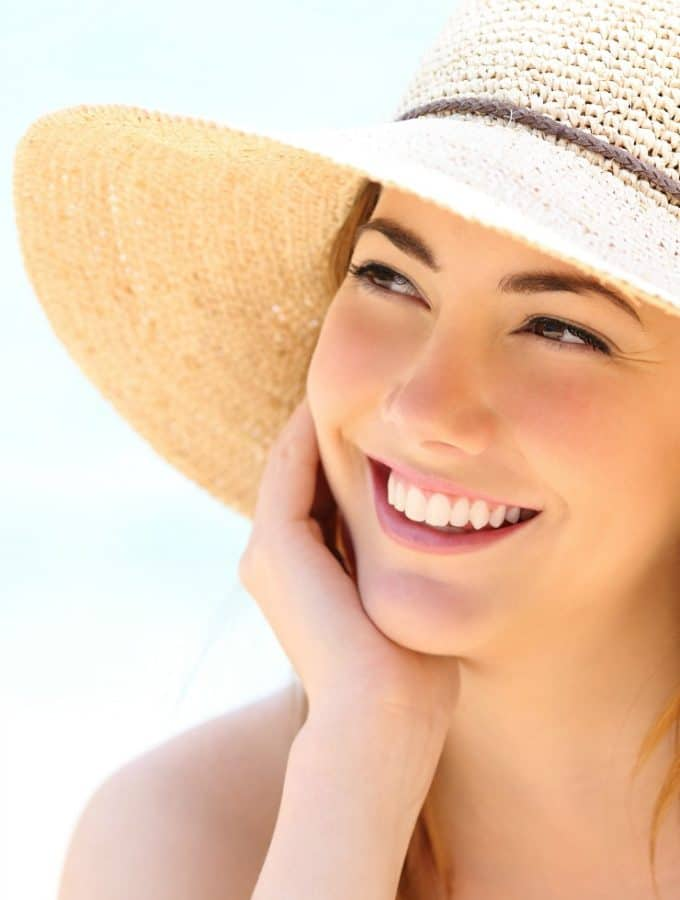 happy young woman on beach with sun hat