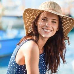 Beautiful brunette woman on boat dock wearing straw hat
