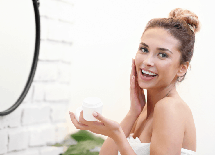 Pretty young woman applying face cream in front of bathroom mirror